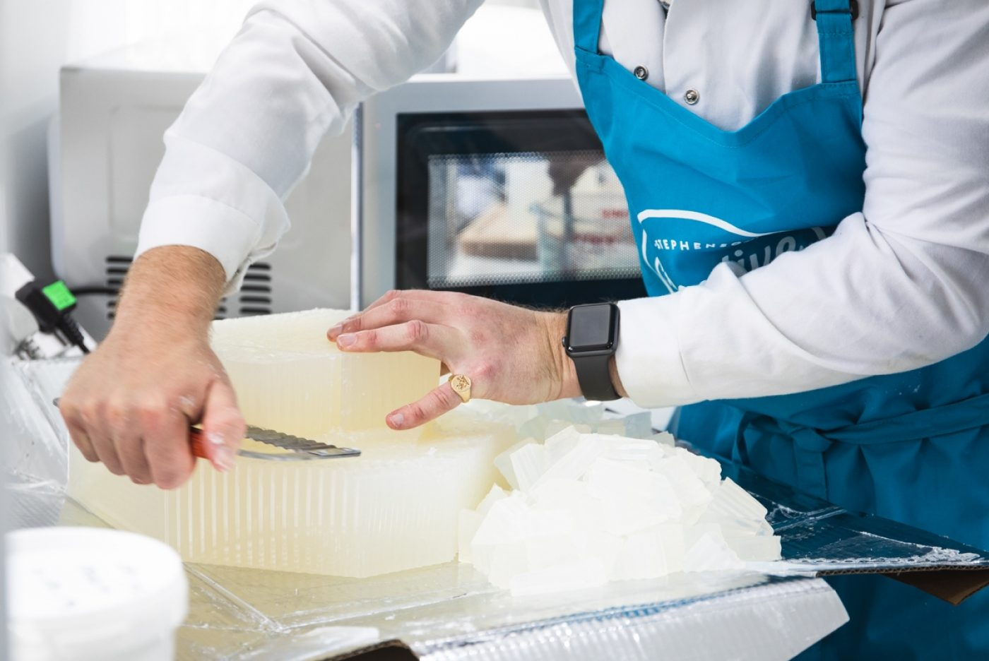 Person in white coat and blue apron cutting a large block of soap.