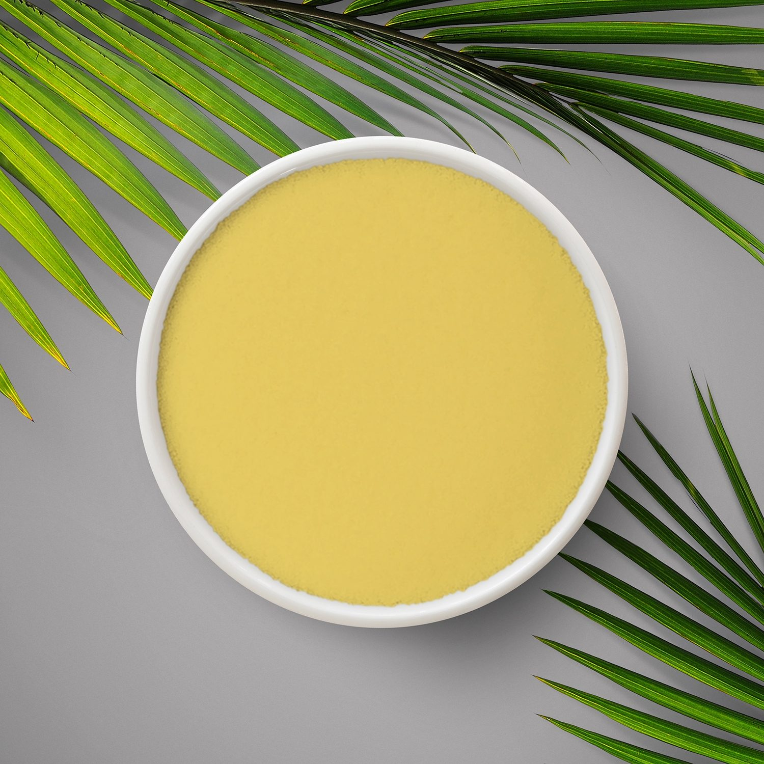 Fine wax powder with yellowish colour and pine leaves around the edge.