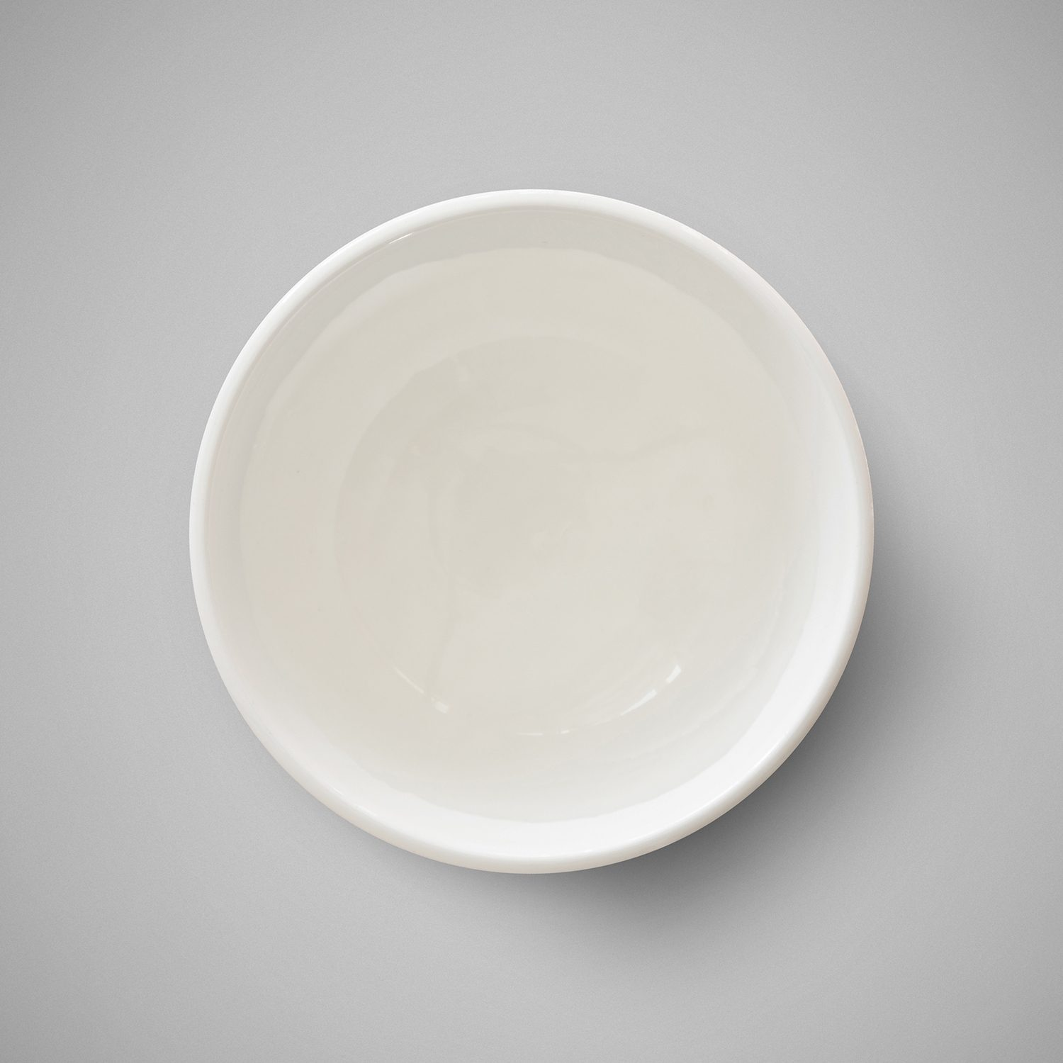 White melt and pour soap base in a small bowl on a grey background.