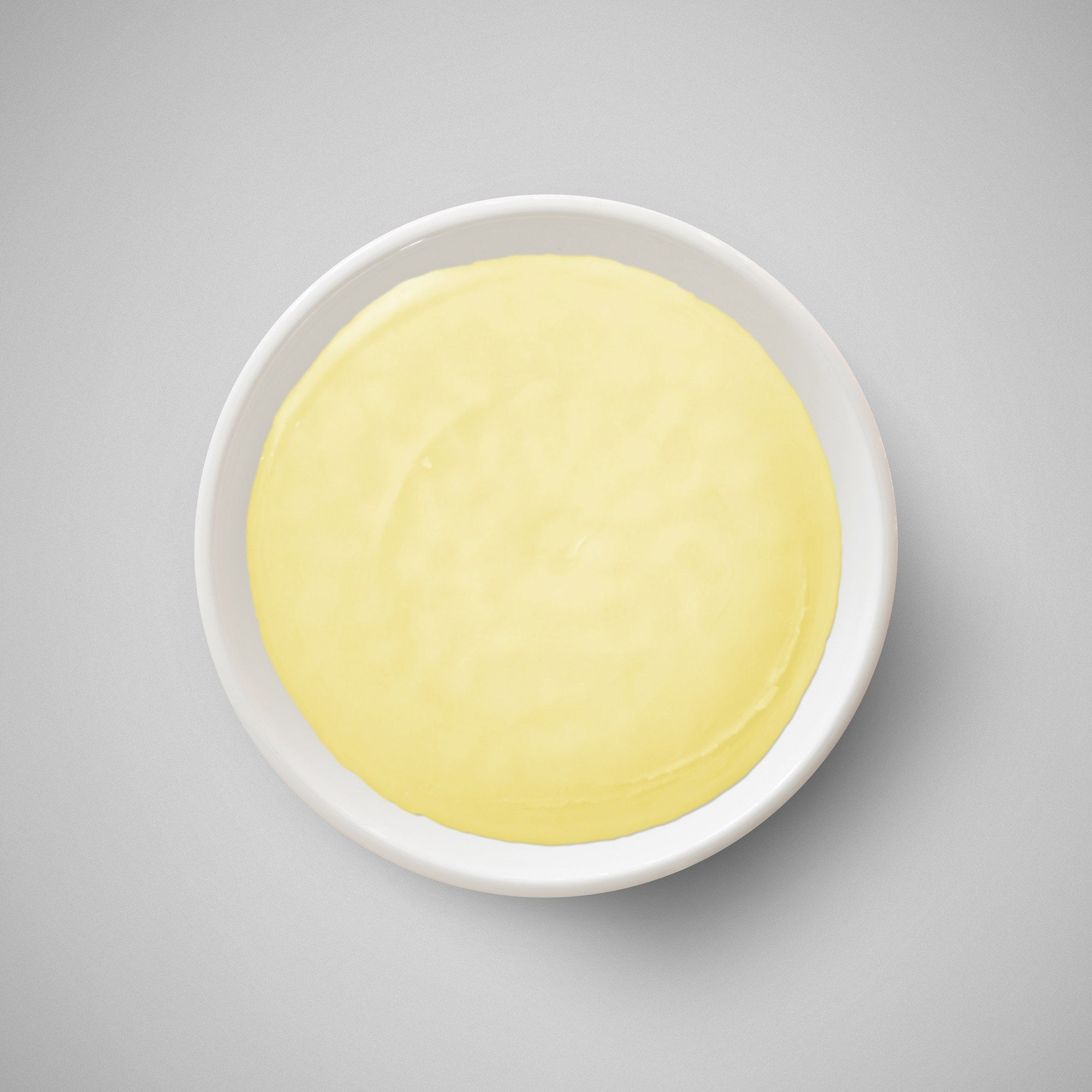 Yellowish creamy substance for making lipstick in a small bowl against a grey background.