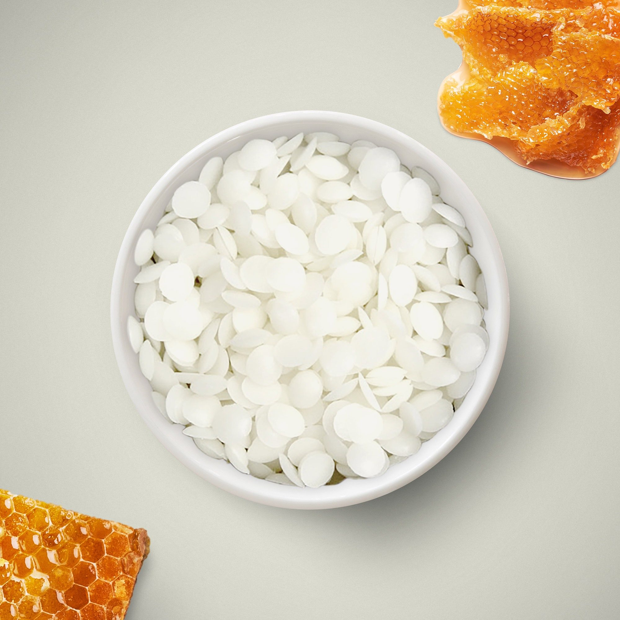 White beeswax beads in a bowl against a white background, with honeycomb around the edges.