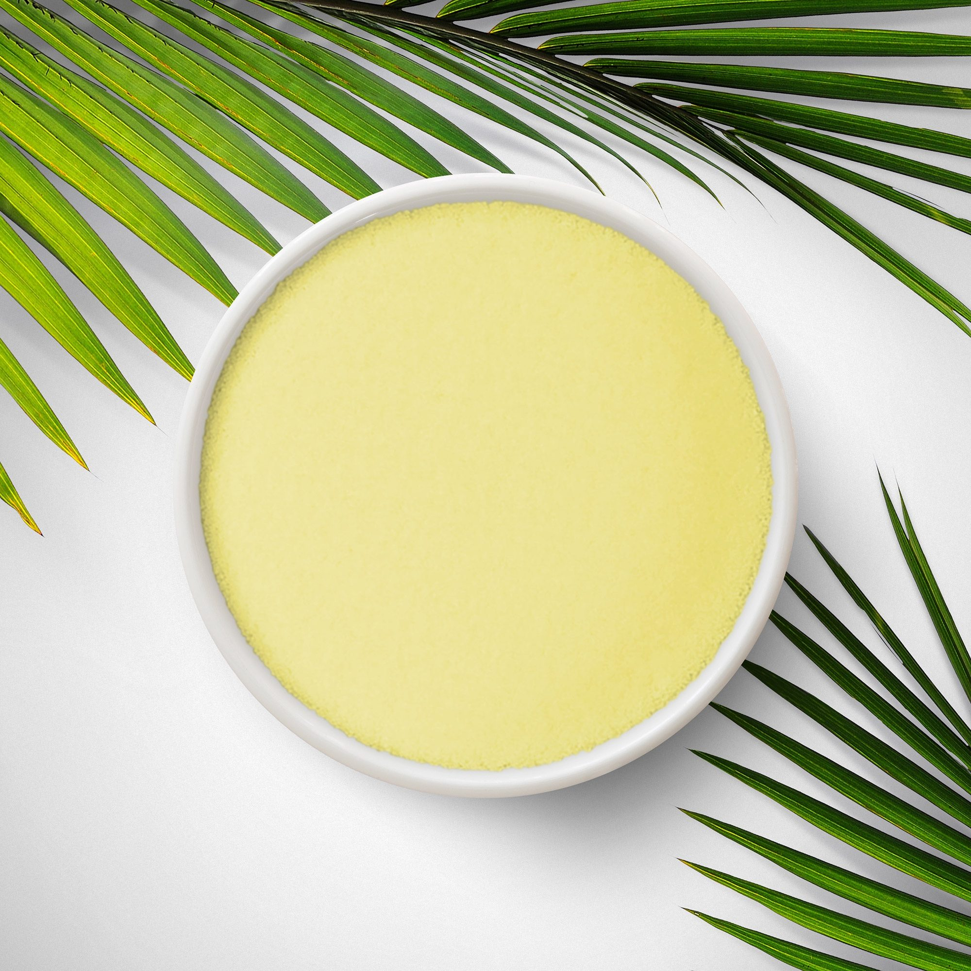 Yellow fine powder in a small white bowl with palm leaves on the edge.