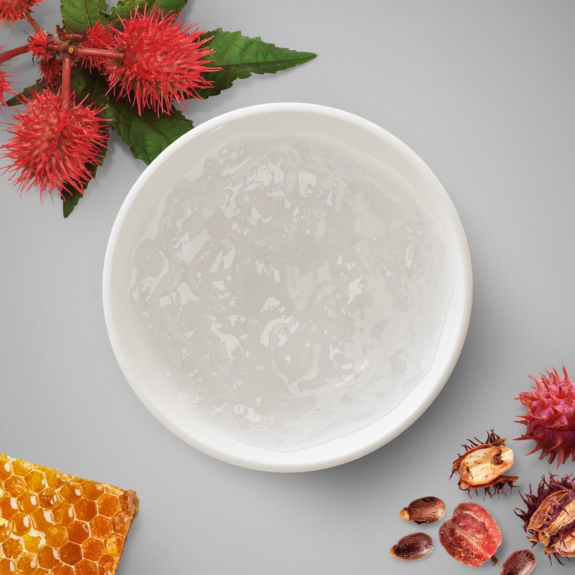 Clear, thick jelly in a small bowl with red flowers and honeycomb on the outside.