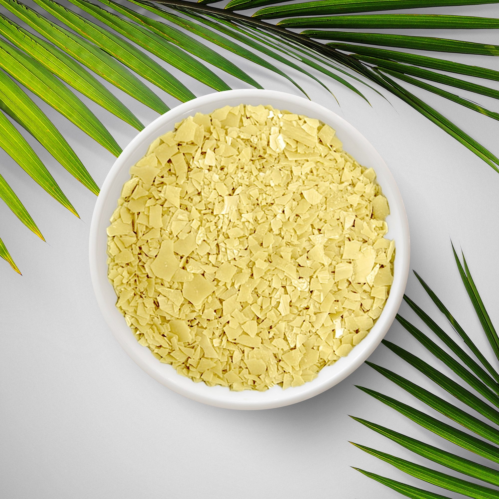 Yellow flakes of wax in a small bowl with palm leaves around the edge – supplied by H Foster.